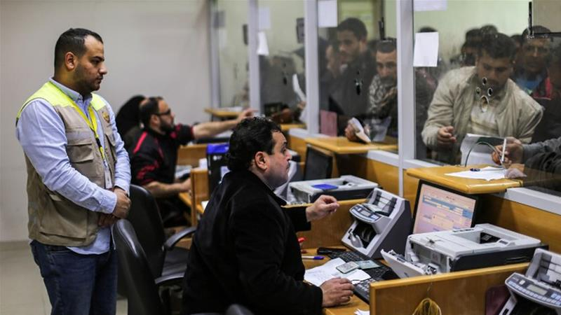 Palestinians at the central post office in Gaza City received financial aid from the Qatari government [Mahmud Hams/AFP]