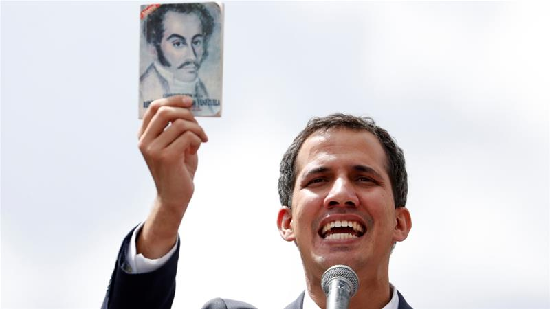 National Assembly President Juan Guaido holds a copy of the Venezuelan constitution during a rally against Nicolas Maduro's government in Caracas on January 23, 2019 [Reuters/Carlos Garcia Rawlins]