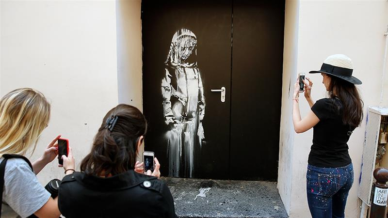 Young women take a picture of an artwork in Paris attributed to street artist Banksy that was stolen on Friday [Chesnot/Getty Images]