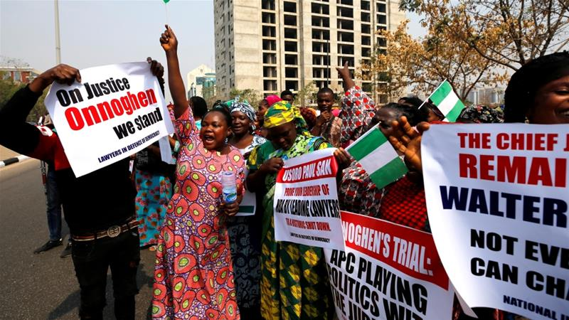 Nigerians hold banners during a protest over the suspension of the chief justice [Afolabi Sotunde/Reuters]