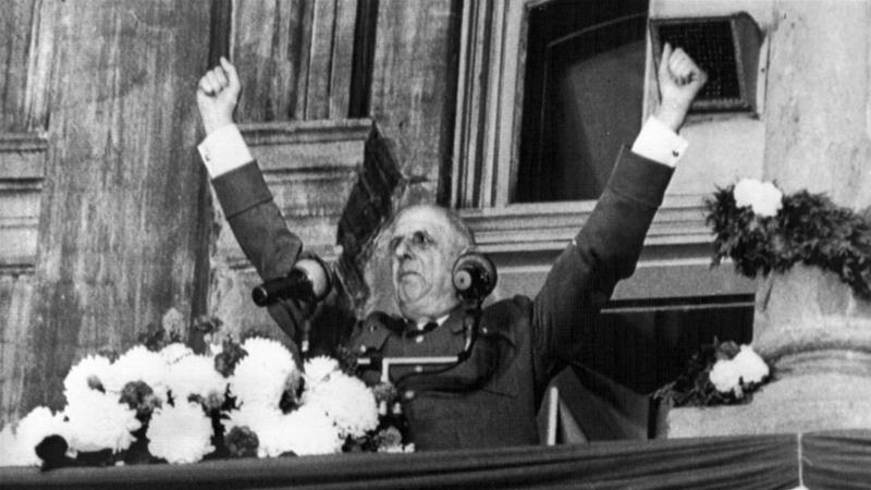 Former French President Charles de Gaulle raises his arms with fists closed as he speaks from the balcony of Montreal City Hall, Quebec on July 25, 1967 [File: AP photo]