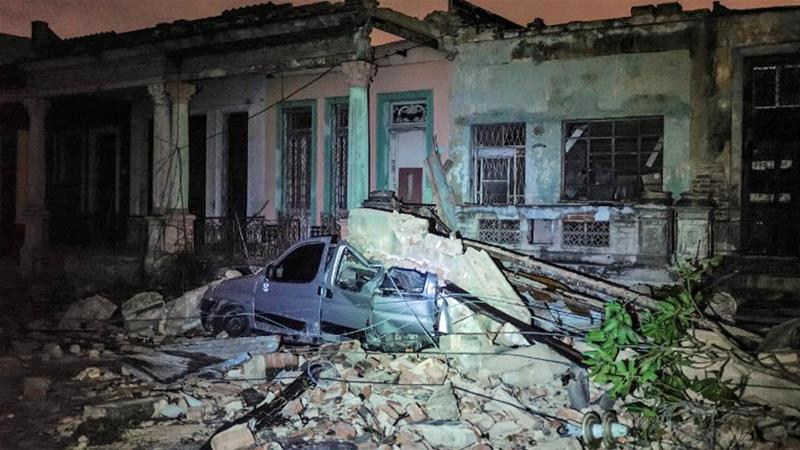 A damaged car flattened by debris from a building is seen in the tornado-hit Luyano neighbourhood in Havana [Adalberto Roque/AFP]