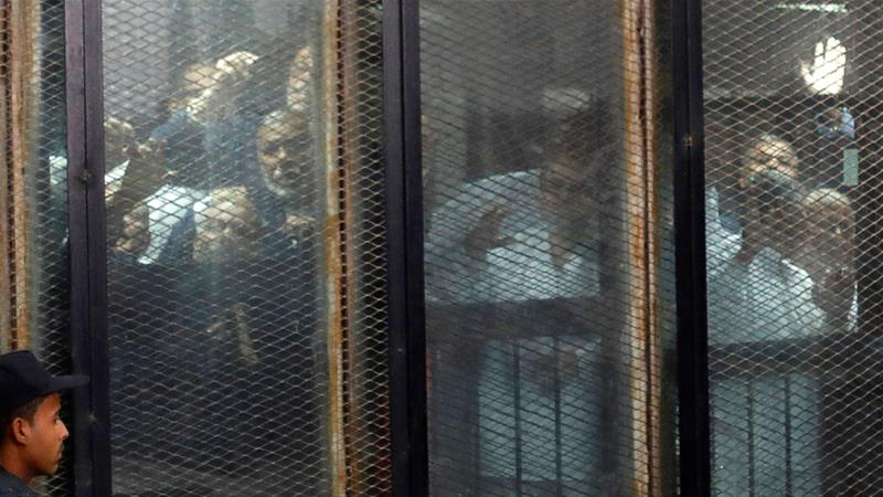 Muslim Brotherhood members are seen behind bars during a court session in Cairo [File: Amr Abdallah Dalsh/Reuters]