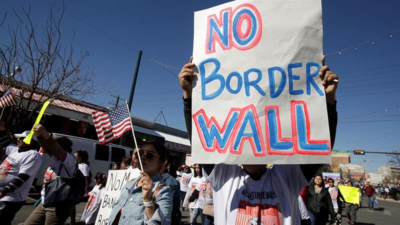 A man holds a sign during a march against building a wall on US-Mexico border [File: Jose Luis Gonzalez/Reuters]