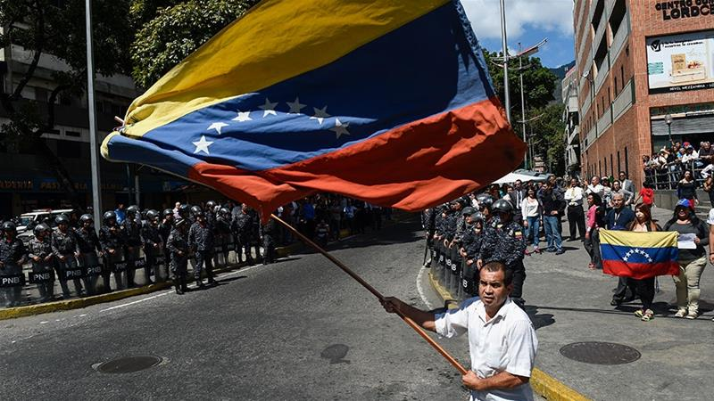 An opposition demonstrator waves a Venezuelan national flag, during a protest against the government of President Maduro [Federico Parra/AFP]