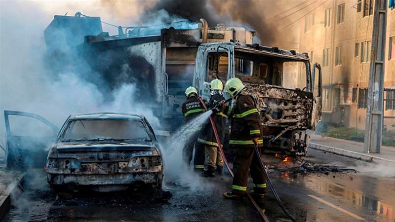 Firefighters put out a burning truck and car during a wave of gang violence in Brazil's northeastern city of Fortaleza [Alex Gomes/AFP]