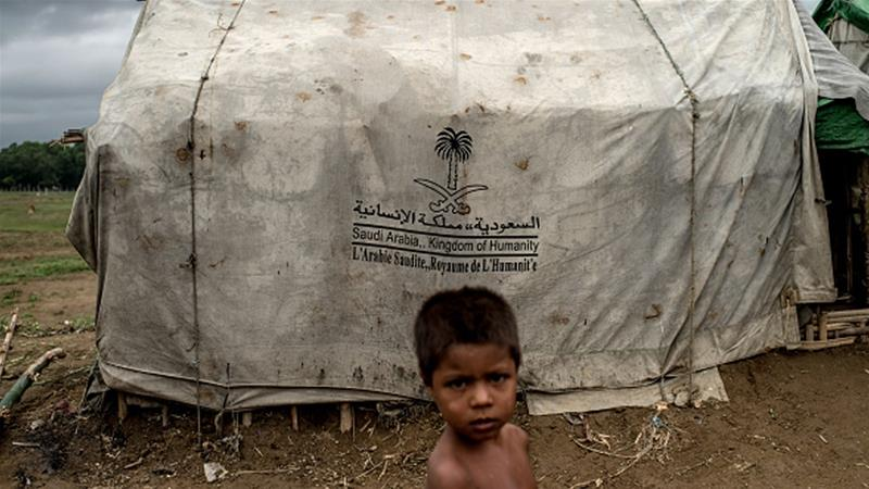 A boy stands in front of a tent donated by Saudi Arabia at one of the IDP camps in Sittwe, Myanmar [File: Jonas Gratzer/Getty Images]