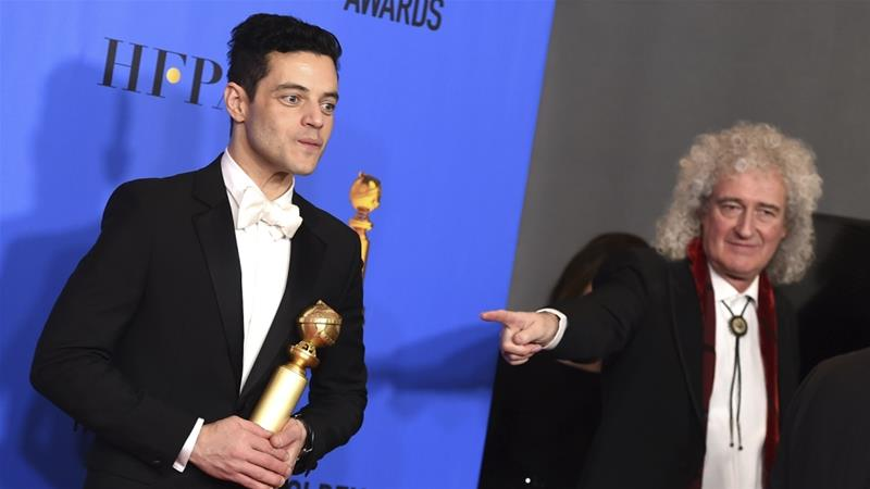 Rami Malek, left, poses with his award with Queen's Brian May [Jordan Strauss/AP]