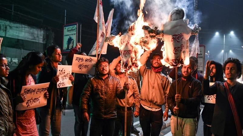Protesters set fire to effigies of the prime minister and vandalised two BJP offices [Biju Boro/ AFP]