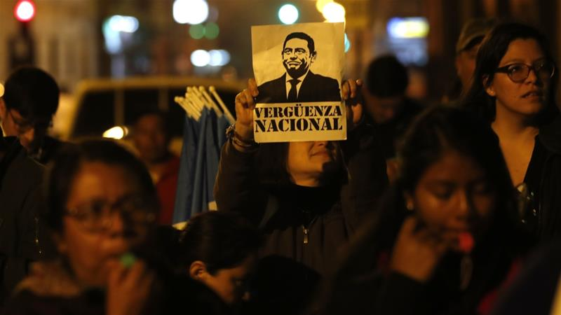 A woman holds up a sign with a portrait of President Jimmy Morales that reads in Spanish 'national shame', during a rally in support of the CICIG in Guatemala City on January 8 [Moises Castillo/AP]