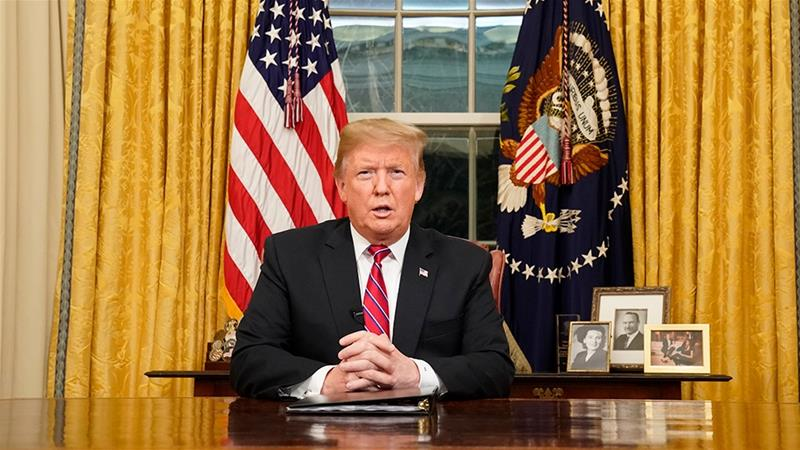 Trump delivers a televised address to the nation from his desk in the Oval Office [Carlos Barria/Reuters]