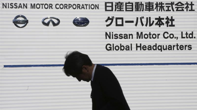 A man walks past corporate logos at the global headquarters of Nissan Motor Company in Yokohama [Koji Sasahara/AP]