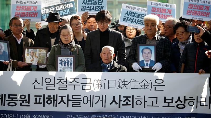 Lee Choon-shik, a victim of wartime slavery, arrives for a court hearing in October as supporters hold portraits of forced labour victims and banners urging Nippon to apologise and pay compensation [File: Kim Hong-Ji/Reuters]