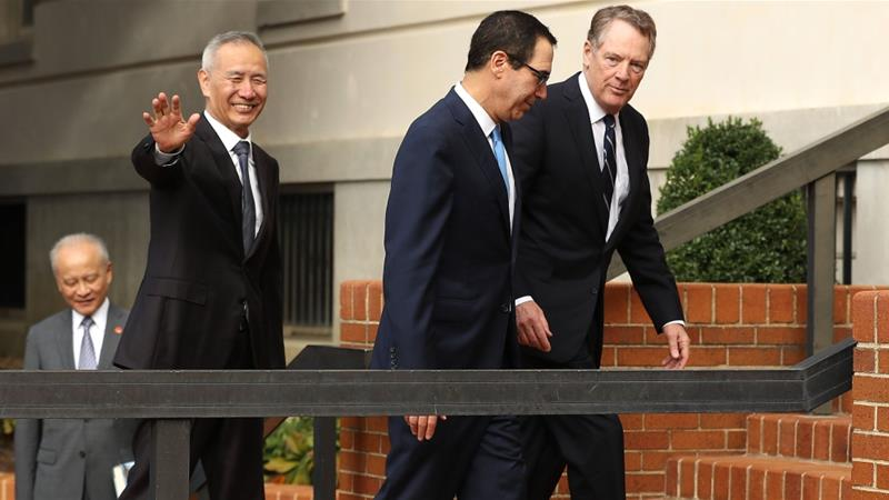 Chinese Vice Premier Liu He, waving, is escorted by US Trade Representative Robert Lighthizer, right, and Treasury Secretary Steven Mnuchin into the USTR offices [Chip Somodevilla/Getty Images/AFP]