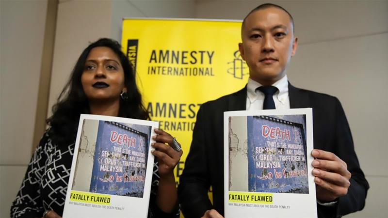 Representatives from Amnesty hold copies of a report on the state of death penalty cases in Malaysia on Thursday [Sadiq Asyraf/AFP]