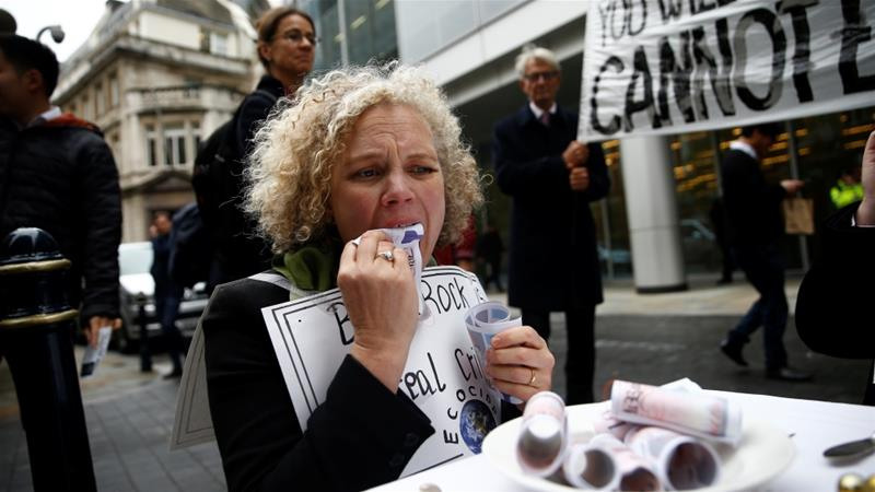 A protester eats fake money outside the BlackRock office during Extinction Rebellion demonstrations in London [Henry Nicholls/Reuters]