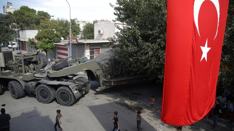 Turkish military equipment is transported on a street in the Turkish border town of Akcakale [Stoyan Nenov/Reuters]