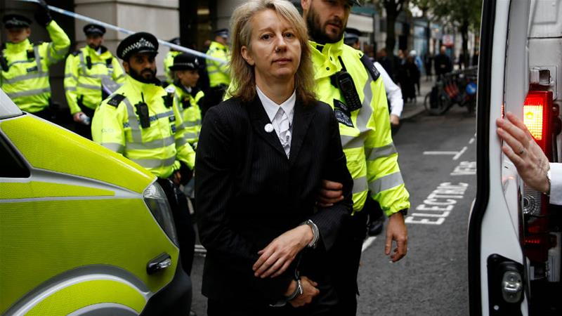 Gail Bradbrook, a co-founder of Extinction Rebellion, is led away in handcuffs having been removed from the entrance to the UK Department of Transport [Henry Nicholls/Reuters]