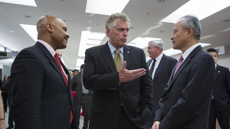 China's Ambassador to the USA Cui Tiankai (right) speaks to Terry McAuliffe (centre), governor of the US state of Virginia and another state official [File: Jim Lo Scalzo/EPA]