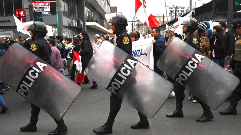 Police stay alert as demonstrators march against corruption in Lima on Monday [Cris Bouroncle/AFP]