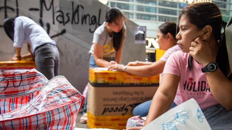 Women pack boxes to ship back to the Philippines in Central, Hong Kong's business district and the site of several anti-government protests over the past four months [Betsy Joles/Al Jazeera]