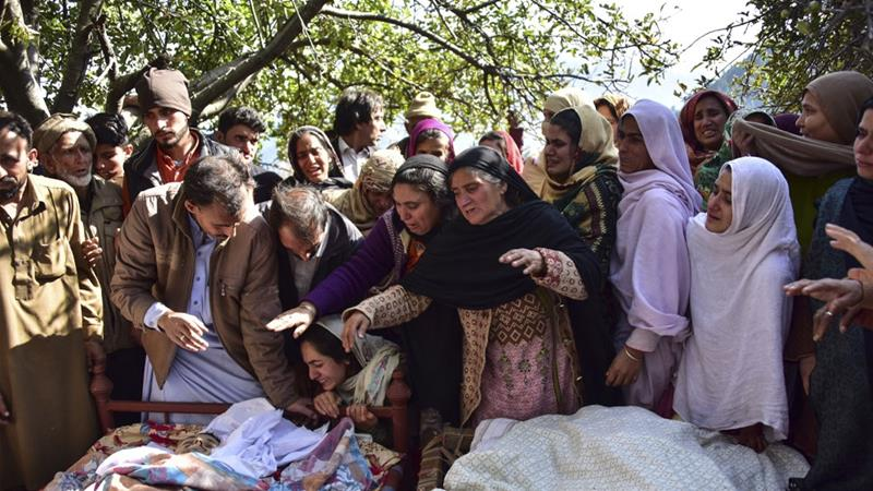Relatives and friends mourn next to bodies of victims in cross border shelling in Pakistan's Neelum valley [Sajjad Qayyum/AFP]
