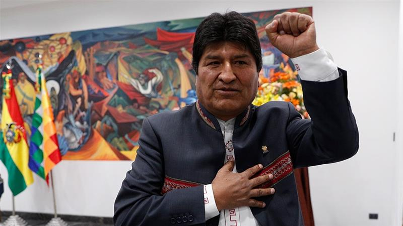 Bolivia's President Evo Morales raising his arm after declaring himself the winner of the country's presidential election in a news conference in La Paz [Juan Karita/AP]
