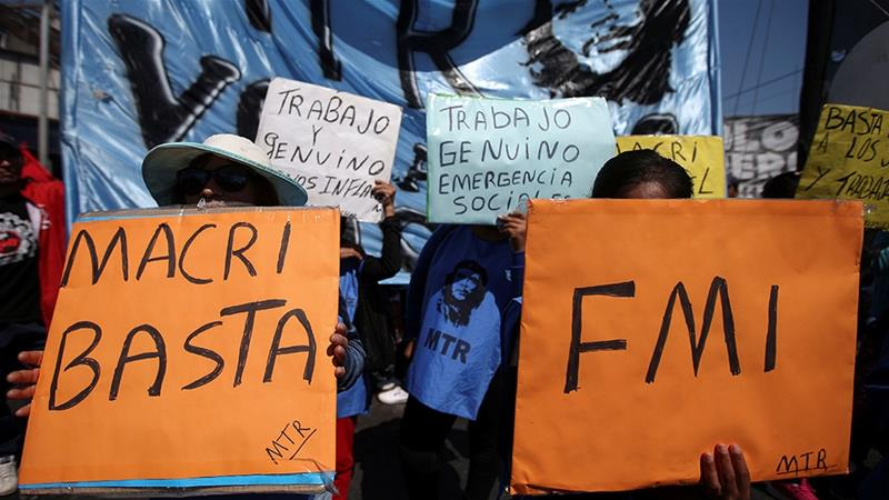 "During a September demonstration against incumbent Argentine President Mauricio Macri's economic policies, people hold placards reading ""Macri, Stop"" and ""IMF"" [File: Agustin Marcarian/Reuters]"