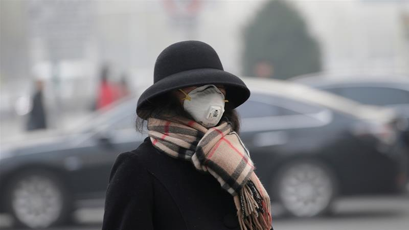 A woman in Beijing during heavy smog last November; China's winter smog targets for 2019 will not be enough to offset last year's increase in pollution, according to government data [File: Jason Lee/Reuters]