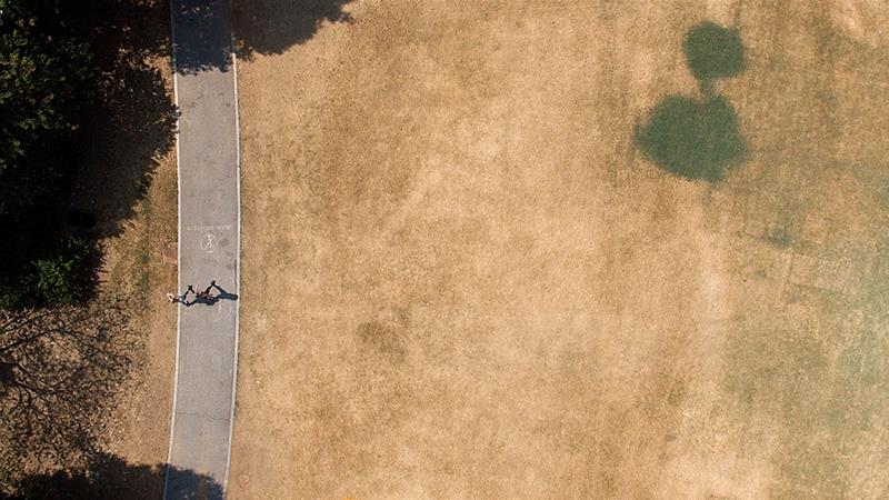 Pedestrians walk past a patch of green grass amidst a dry lawn, which has turned brown from a lack of rain in Atlanta [David Goldman/AP Photo]