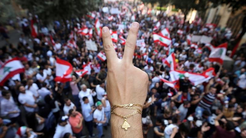 A demonstrator flashes a V sign during an anti-government protest in downtown Beirut, Lebanon October 21, 2019. [Ali Hashisho/Reuters]