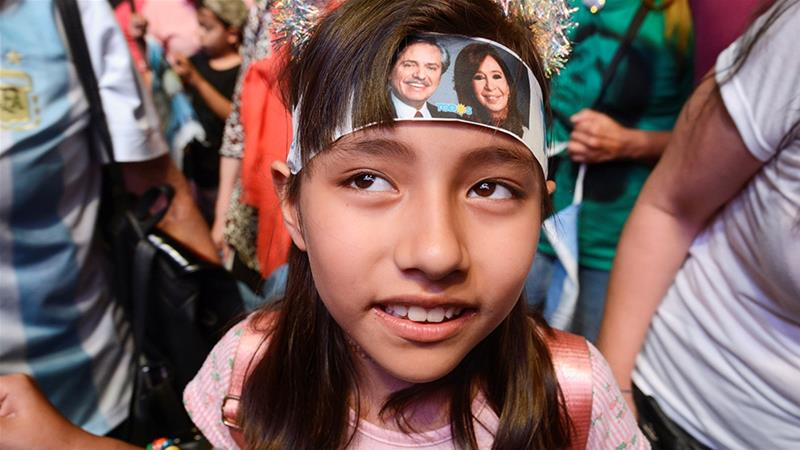A child wears a headband with photographs of Argentina's President-elect Alberto Fernandez and his running mate and former President Cristina Fernandez de Kirchner, who now face the daunting task of reviving the country's moribund economy [File: Magali Druscovich/Reuters]