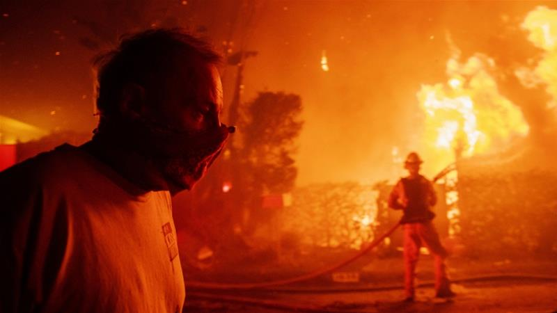 A man walks past a burning home in Los Angeles [Christian Monterrosa/The Associated Press]