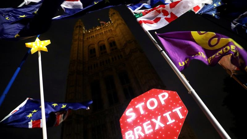 A sign reading 'Stop Brexit' is pictured as flags flutter outside the Houses of Parliament in London [Simon Dawson/Reuters]