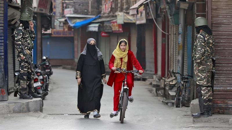 A Kashmiri girl rides her bike past Indian security forces guarding a street in Srinagar [Danish Ismail/Reuters]