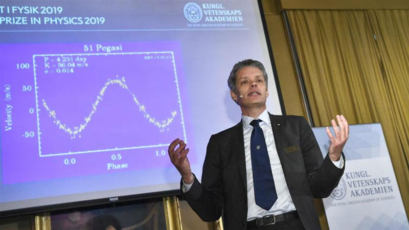Ulf Danielsson of the Nobel committee announces the winners of the 2019 Nobel Prize in Physics [Claudio Bresciani/EPA]