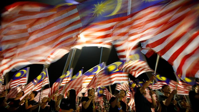 People from Sabah wave Malaysian flags during the Malaysia Day celebrations in 2012. [Bazuki Muhammad/Reuters]