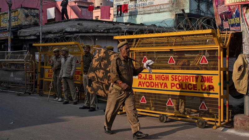 A police officer walks past a security barricade as others stand guard near a temple after Supreme Court's verdict on a disputed religious site in Ayodhya [Danish Siddiqui/Reuters]
