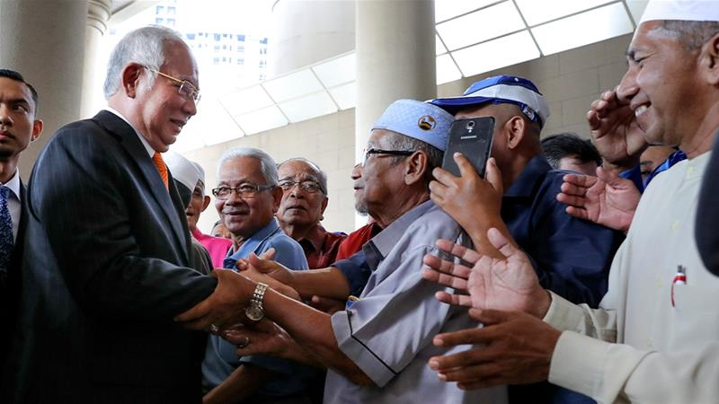 Former Malaysian Prime Minister Najib Razak, left, greets supporters as he arrives at the Kuala Lumpur High Court where a judge ruled that he must enter his defence in the first of a series of corruption trials in relation to state fund 1MDB [Vincent Thian/AP Photo]
