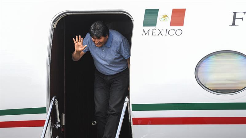 Former Bolivian President Evo Morales waves upon landing in Mexico City, where he was granted exile after his resignation [Pedro Pardo/AFP]