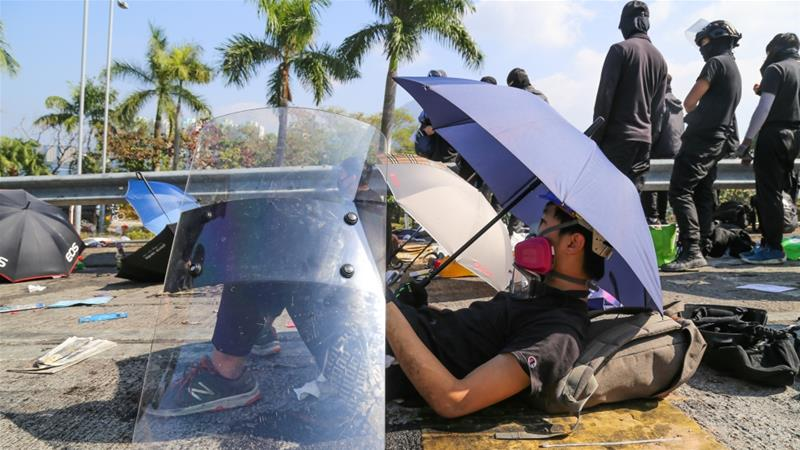 A protester rests under an umbrella at the site of a bloody face-off with police on Tuesday [Betsy Joles/Al Jazeera]