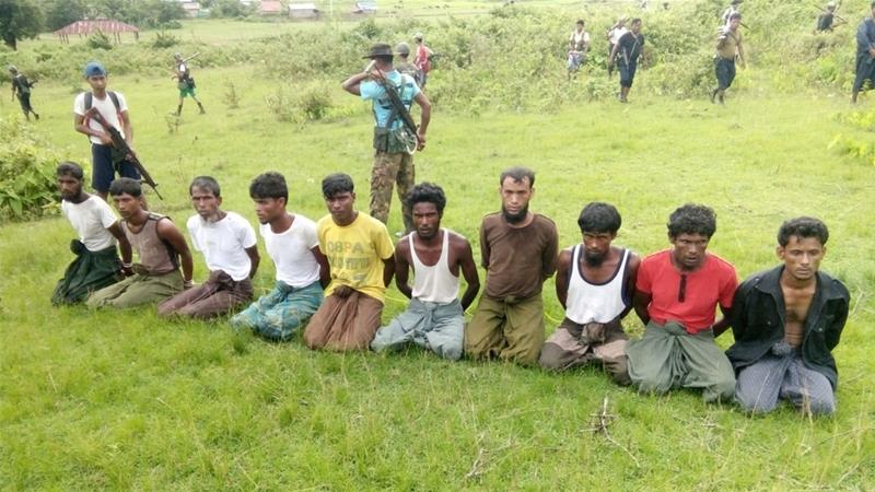 Rohingya men kneel as members of Myanmar's security forces stand guard in Inn Din village in September 2017 [Reuters]