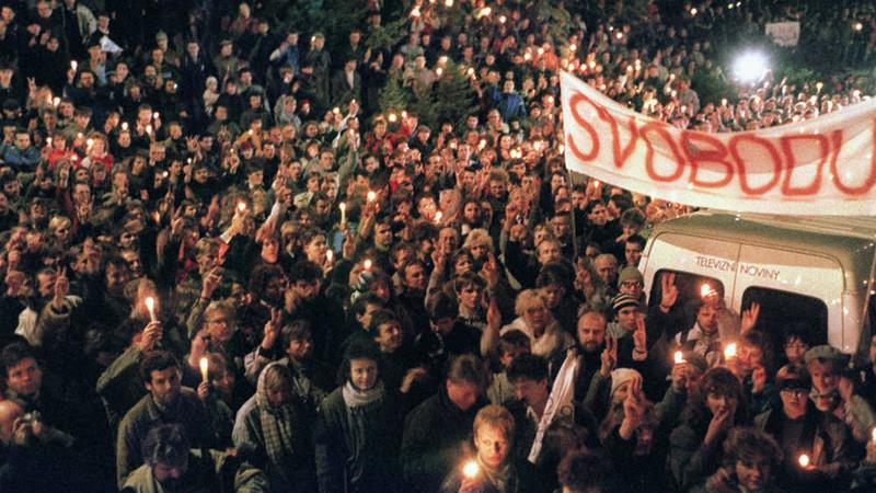 Young Czechoslovak students make victory sings and light candles on 17 November 1989 as the Velvet Revolution unfolds. The banner reads: 'Liberty' [Lubomir Kotek/AFP]
