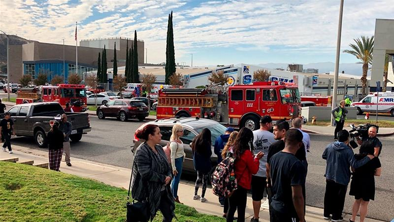 People wait for students and updates outside of Saugus High School after reports of a shooting [Marcio Jose Sanchez/AP Photo]