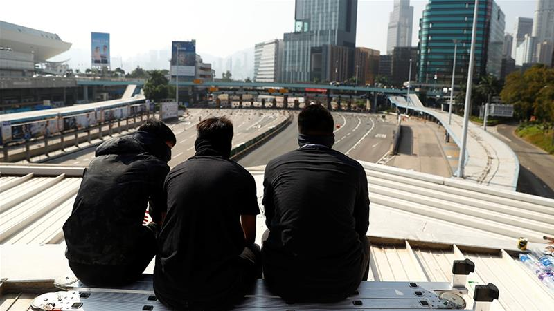 Protesters sit on the roof of a bridge overlooking the blocked Cross Harbour Tunnel. [Thomas Peter/Reuters]