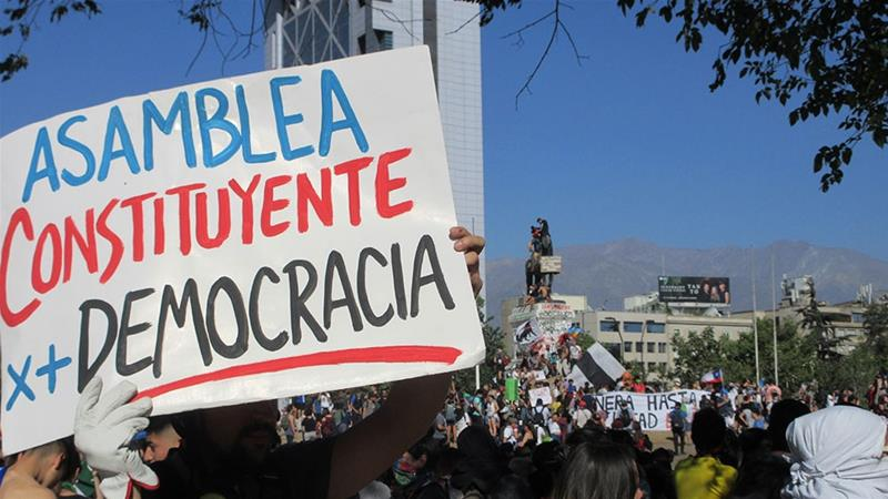 A protester in Santiago holds a sign calling for a 'constitutional assembly for more democracy' [Sandra Cuffe/Al Jazeera]