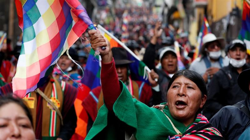 A supporter of former Bolivian President Evo Morales holding a Wiphala flag takes part in a protest in La Paz [Carlos Garcia Rawlins/Reuters]