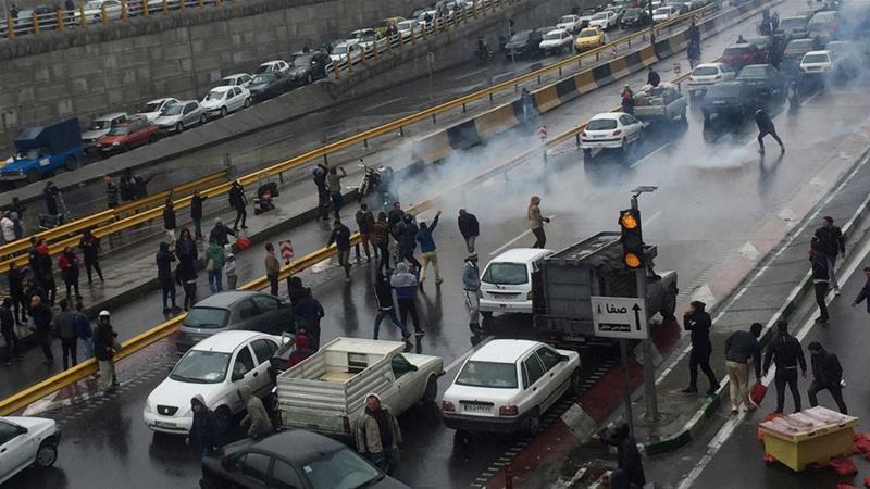 People protest against a hike in petrol prices on a highway in Tehran [WANA via Reuters]