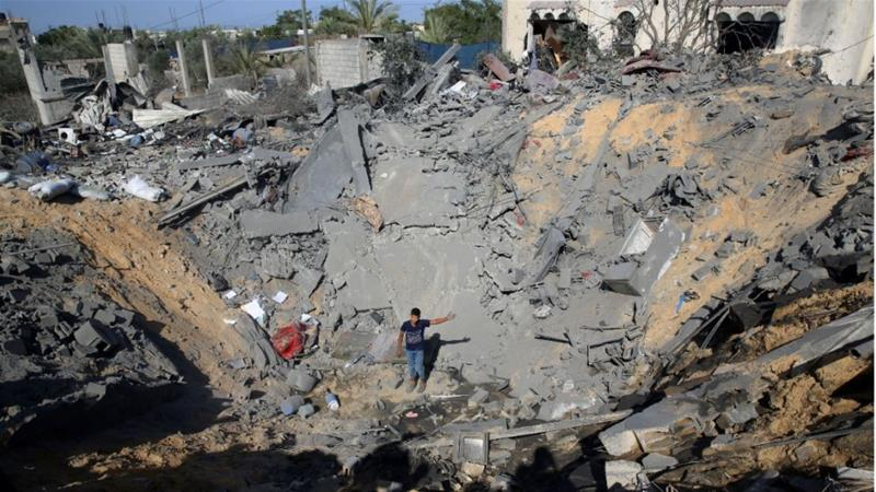 A young Palestinian stands amid the crater of a destroyed house following overnight Israeli missile attacks on Thursday east of Khan Younis [Adel Hana/AP Photo]