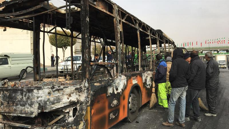 People gather around the wreckage of a public bus on Sunday that was torched during the protests [EPA-EFE]